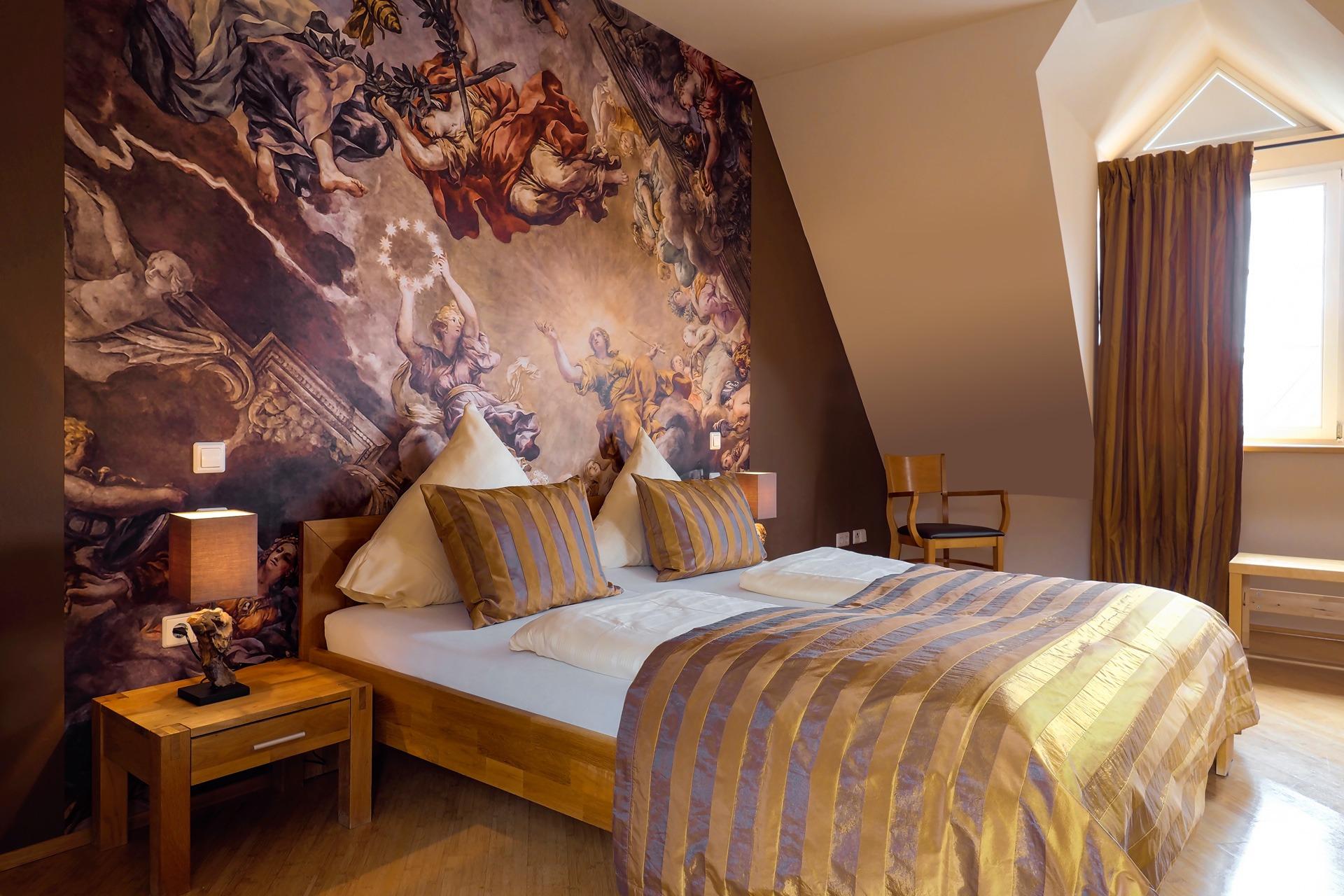 Suite mit Blick auf ein Doppelbett mit Wandbild in warmen Brauntönen